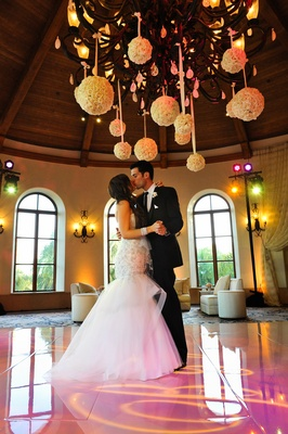 Bride and groom kiss on pink dance floor under rose balls