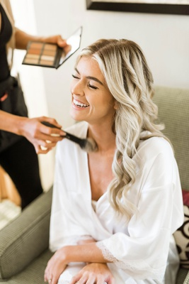bride in white robe getting makeup done makeup artist brush long blonde hair laughing