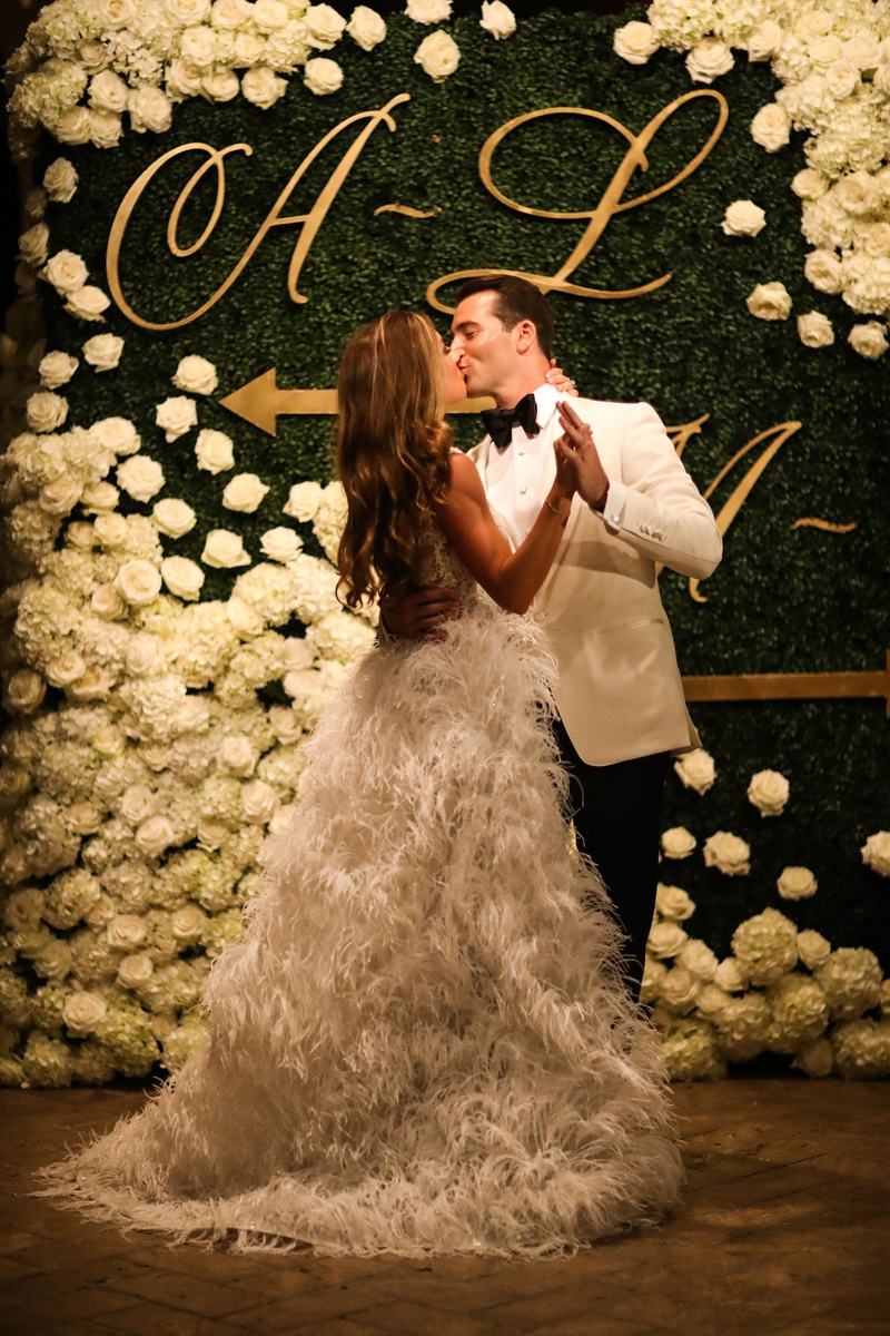 bride in second wedding dress ostrich feather skirt kissing groom in front of hedge wall chart