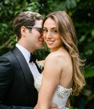 Groom in Tom Ford tuxedo bow tie glasses holds bride in strapless Oscar de la Renta wedding dress