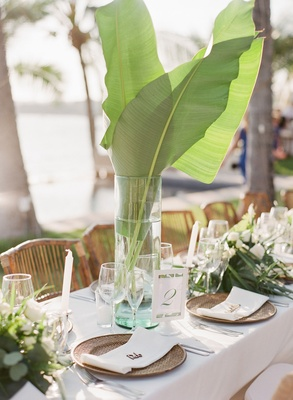Tropical destination wedding centerpiece palm leaves in tall vase rattan charger plates greenery