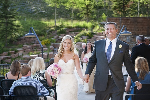 Bride and groom hold hands as they walk up aisle as husband and wife in outdoor ceremony