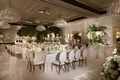 wedding reception white linen metallic chairs chandeliers greenery gold mirrors ballroom reception