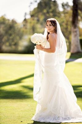 bride in wedding dress and cathedral length veil with bouquet of white flowers