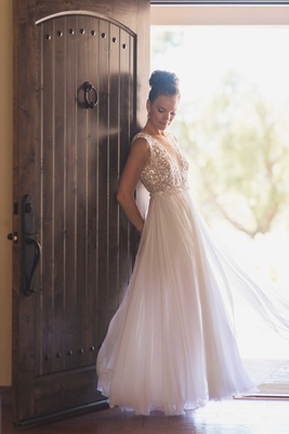 Bride by rustic door wearing Mira Zwillinger sheath wedding dress from Carine's Bridal Atelier bun
