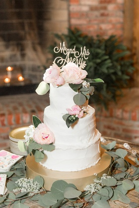 White wedding cake made by the bride on gold stand fresh peony flowers and eucalyptus silver dollar