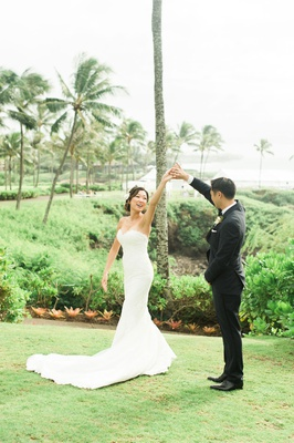 Wedding portrait bride in strapless wedding dress being spun by groom in tuxedo suit hawaii maui