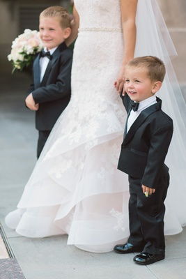 adorable ring bearer in tuxedo holding hands with the bride