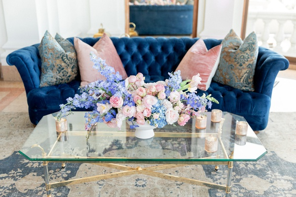 blue tufted velvet sofa with pink pillows, pink and blue floral arrangement, wedding lounge area
