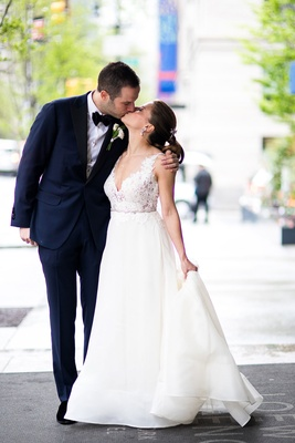 Lace v-neck wedding dress a-line gown from kleinfeld bridal by rivini kissing groom holding train