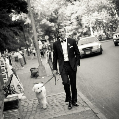 Black and white photo of groom walking dog in NYC