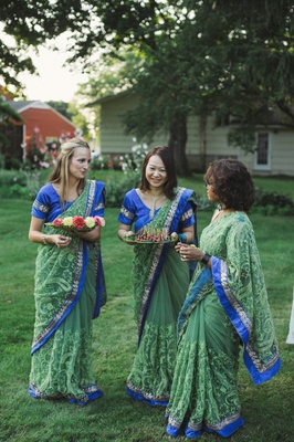 Women in blue and green saris passing food to guests