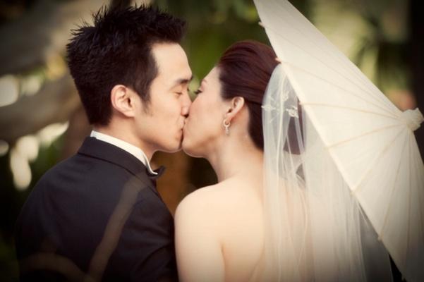 bride and groom kiss under umbrella
