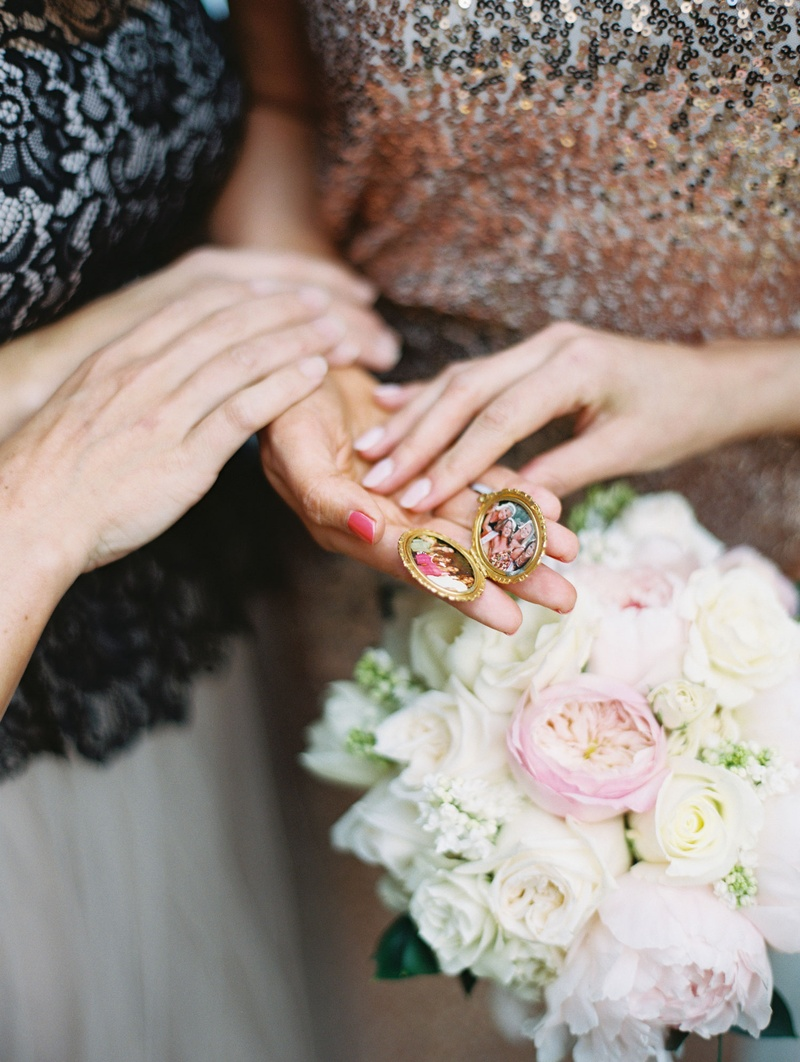 Bride and family holding bouquet and gold locket with photos in it of family