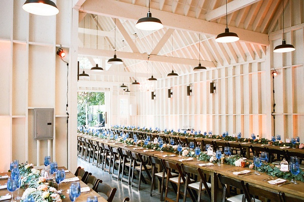 wedding reception at lombardi house in los angeles long farm tables blue glassware greenery