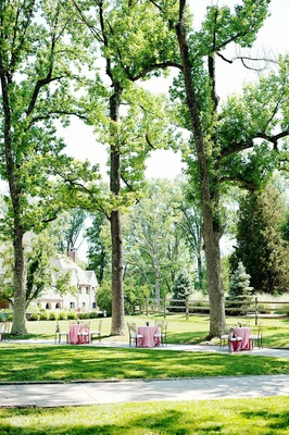 Pink cocktail tables with Chameleon chairs under trees