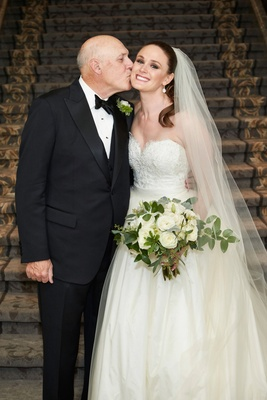 Father of bride in tuxedo bow tie kissing daughter bride on cheek strapless bridal gown