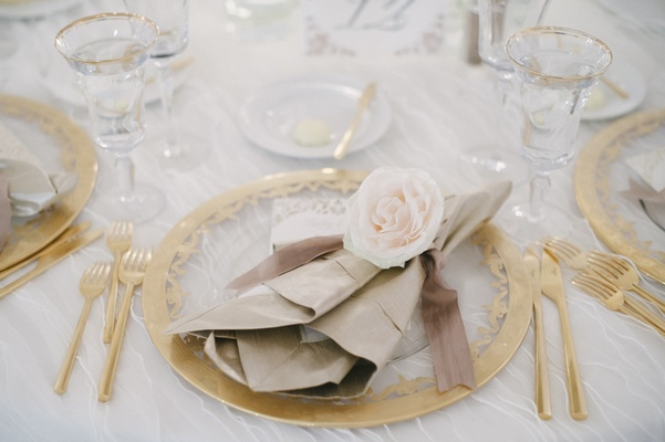 Wedding place setting of gold-rimmed clear charger, champagne flutes, gilt flatware, napkin and rose