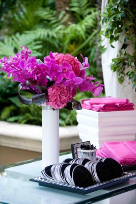 Black yarmulkes with silver borders on table with pink flowers