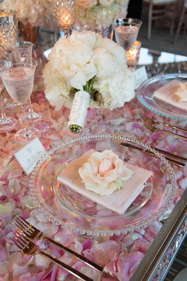 wedding reception place setting rose on top of clear table with layer of rose petals pink
