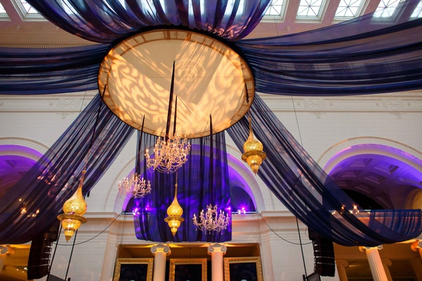 hanging lighting concept and chandeliers with sheer dark blue fabric and purple uplighting