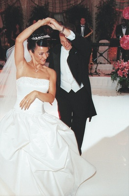Groom spins bride on white dance floor