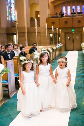 three flower girls in white dresses white flower crowns holding hands down aisle white runner