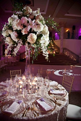 Rosette linens with gold charger plate and tall white flower arrangement