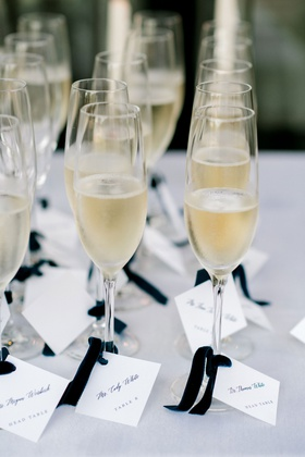 wedding reception champagne in flute glasses blue velvet ribbon with square escort card table number