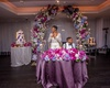 bride and groom behind purple sweetheart table, magenta florals on top, floral arch behind