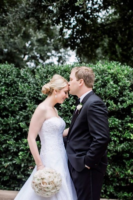groom kissing bride forehead classic wedding strapless dress tuxedo simple white bouquet dallas tx