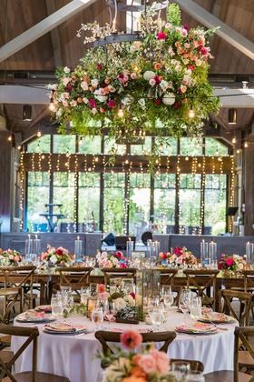 wedding reception wood ceiling high beams chandelier flowers peach pink twinkle lights