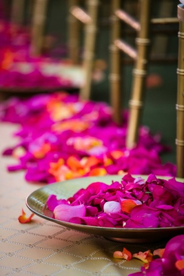 Gold bowls at Indian Hindu wedding ceremony filled with pink and orange flower petals