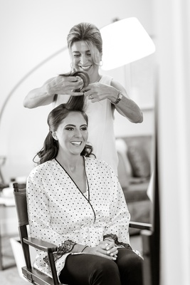 black and white photo bride getting hair done ready before wedding morning of