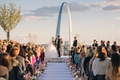 Bride and groom at altar wedding ceremony outside in St. Louis Gateway Arch pink and white flowers