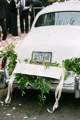 wedding car white with garland of greenery and just married sign tied with ribbon virginia license