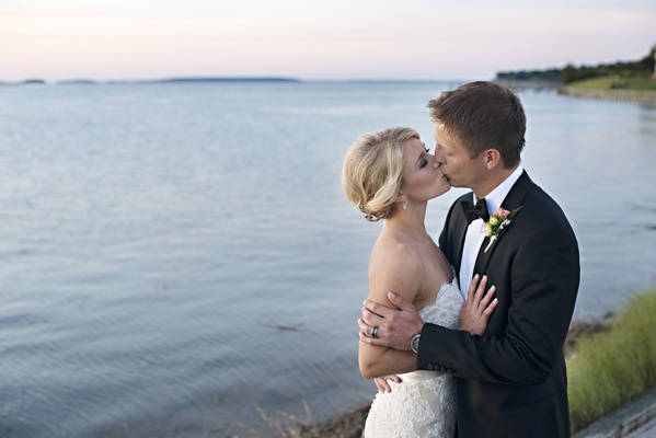 Bride in a lace Anne Barge gown kisses groom in black tuxedo