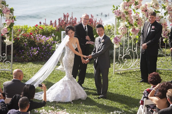 Asian bride and groom hold hands at oceanfront ceremony
