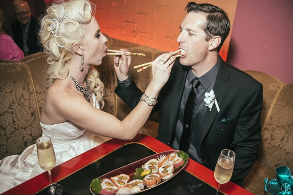 Bride and groom feeding each other sushi rolls