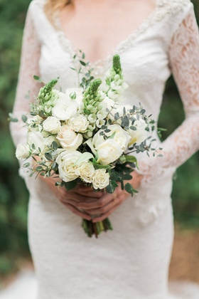 Bride in a long-sleeve Pronovias lace dress holds bouquet of white roses, flowers, and greenery