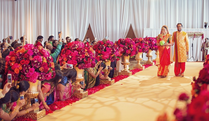 indian wedding, bride and brother in traditional indian wedding attire walk down aisle