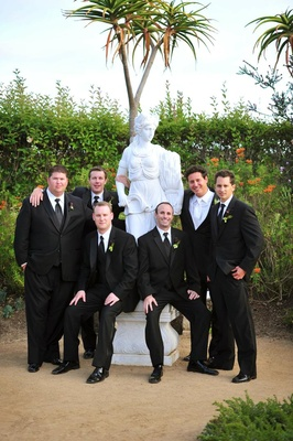 Men in tuxedos next to white statue of woman