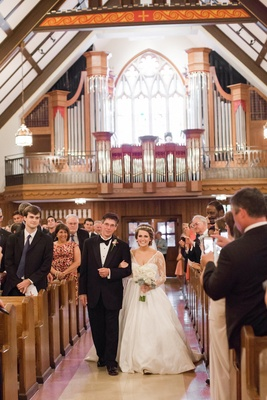 Bride walks down aisle on arm of brother at church