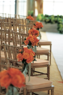 Ceremony chairs decorated with orange rose bouquets and green ribbon