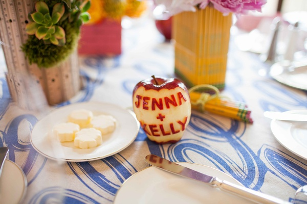 Red delicious apple carved with bride and groom names on bridal shower table decor