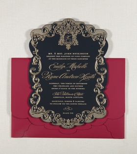 Red scallop envelope with black invitation gold crest and design around border of invitation wedding