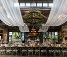 wedding reception long table iron chandelier greenery white drapery vineyard chairs fireplace