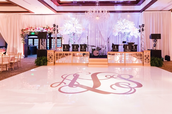 wedding reception white dance floor with giant golden monogram