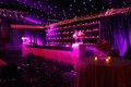 Wedding reception tent with twinkling lights on ceiling, bar with candlelight, violet uplighting