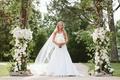 Bride under floral archway in A-line wedding dress